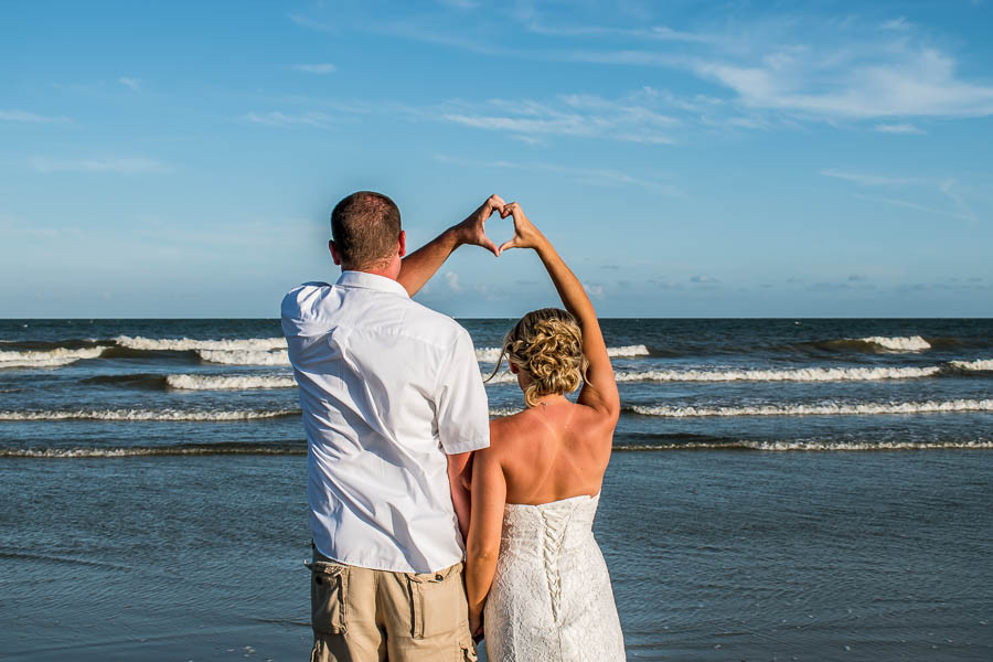 Beach elopement at sunset with newlyweds leaving footprints in the sand