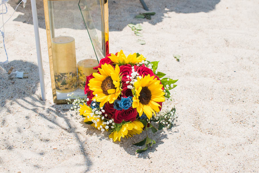 sunflower and red rose bouquet on beach wedding