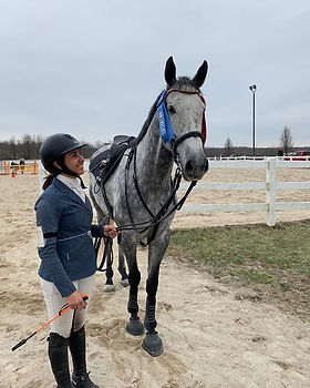 Off the track thoroughbred and trainer compete in hunter/jumper