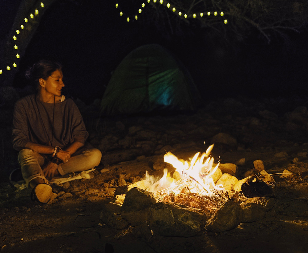 a woman sitting next to a bonfire at the camping spot in Dubai mountains