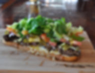 Cheeseburger Tartine, a warm open-faced sandwich. With Tomato, lettuce, pickle, onion with cheese