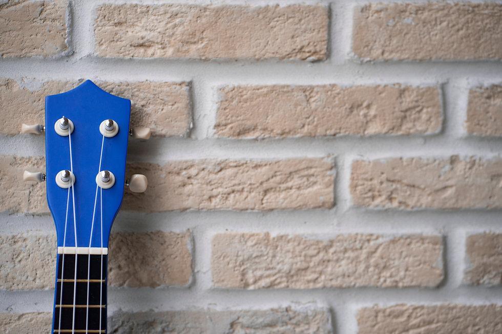 Ukulele blue guitar over brick wall beig
