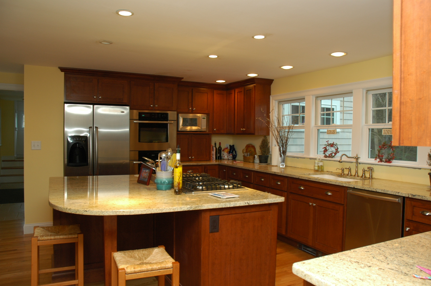 Large-Kitchen-Island-with-Marble-Table-and-Two-Wooden-Chair-also-Wooden-Kitchen-Cabinets-and-Laminat