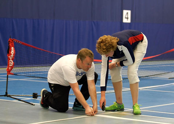 Picture shows volunteers marking out a B1 tennis court