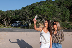 Girls taking a selfie with a helicopter on a Coromandel beach