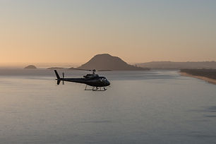 Helicopter flying in a sunrise past the Mount
