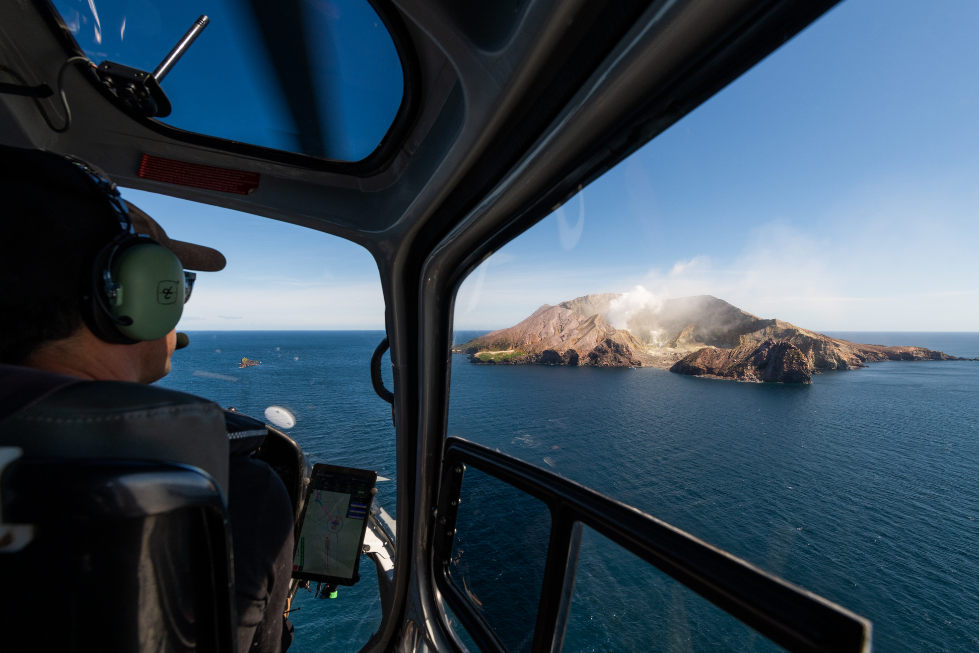 Helicopter pilot flying around White Island Volcano