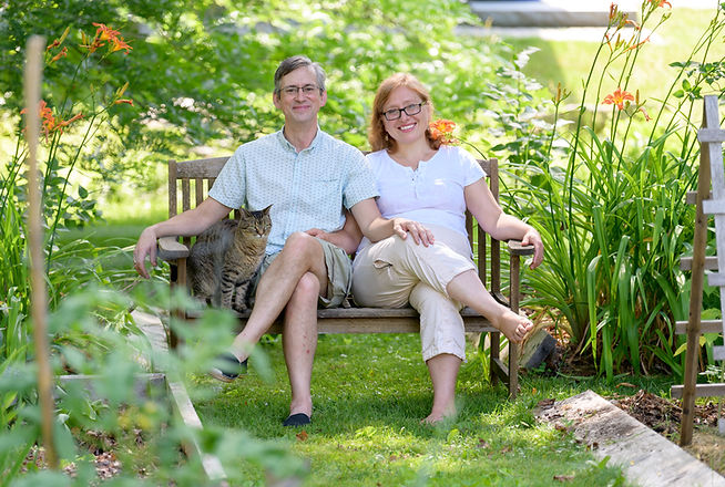 Margot sitting on garden bench surrounded by day lillies with her husband and cat.