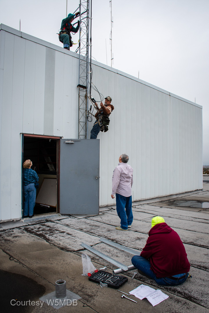 A team effort. Liz, K5EMB, and Dave, N5GDL, supervise tower climbers Ron, NN5R, and Jeri Stone. Meanwhile, Andy, KE5KOF, assembles the tower extension arm for the 2m Winlink antenna.