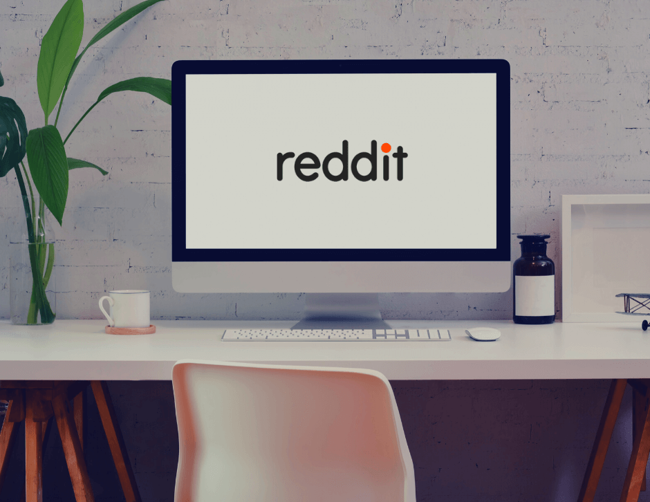 Office desk with a computer displaying Reddit's logo