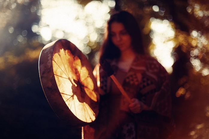 beautiful shamanic girl playing on shaman frame drum in the nature..jpg