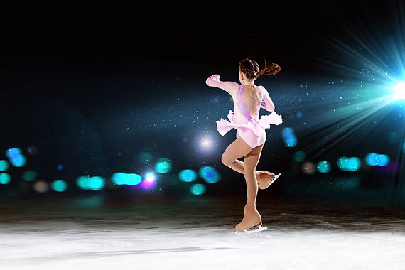 Little girl figure skating at sports arena.jpg