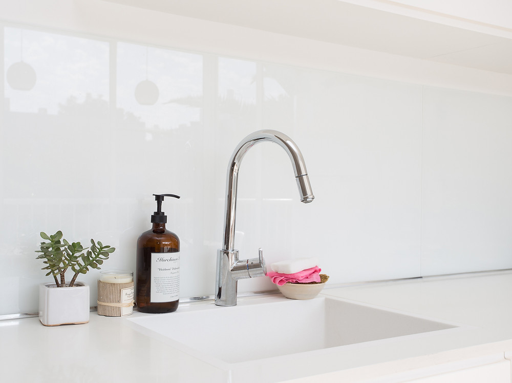 Clean white sink and faucet in kitchen