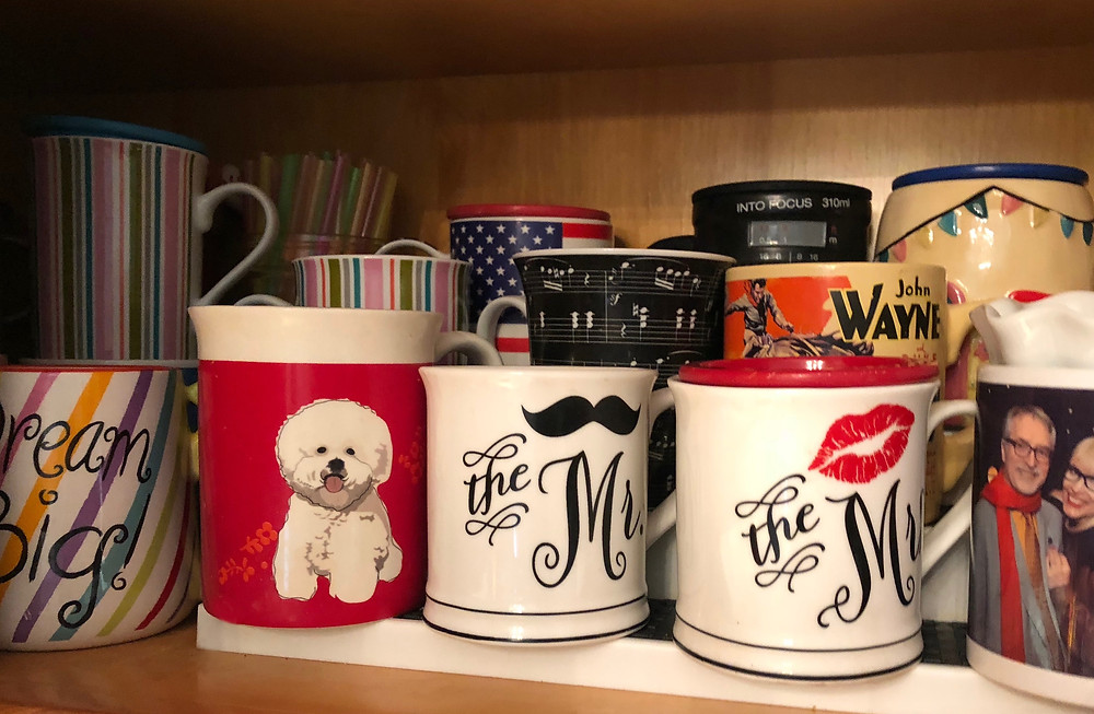 colorful mugs on kitchen shelf
