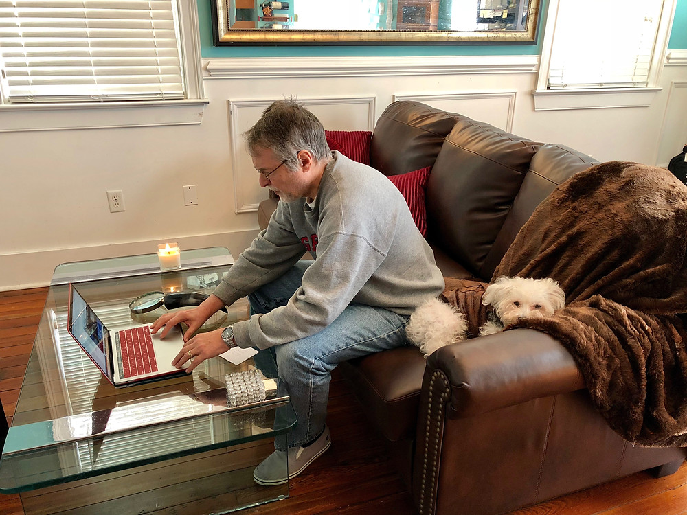 Man working at home on laptop with dog