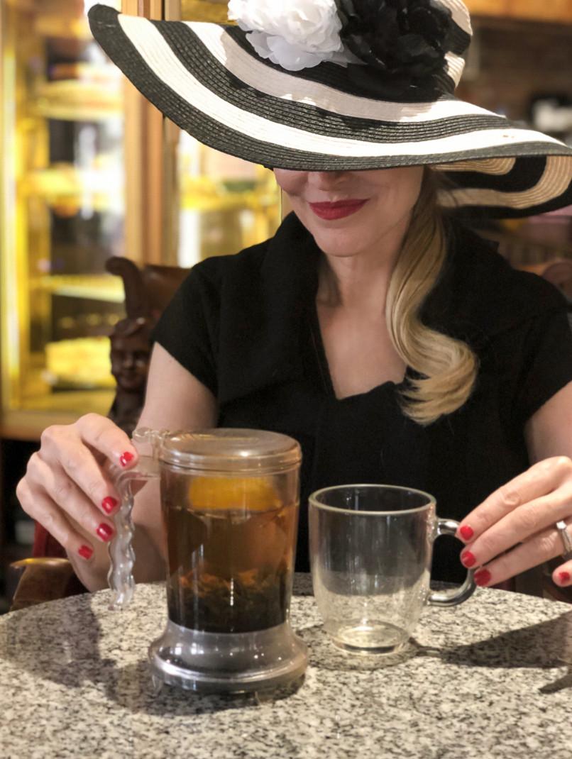 Woman in hat drinking tea