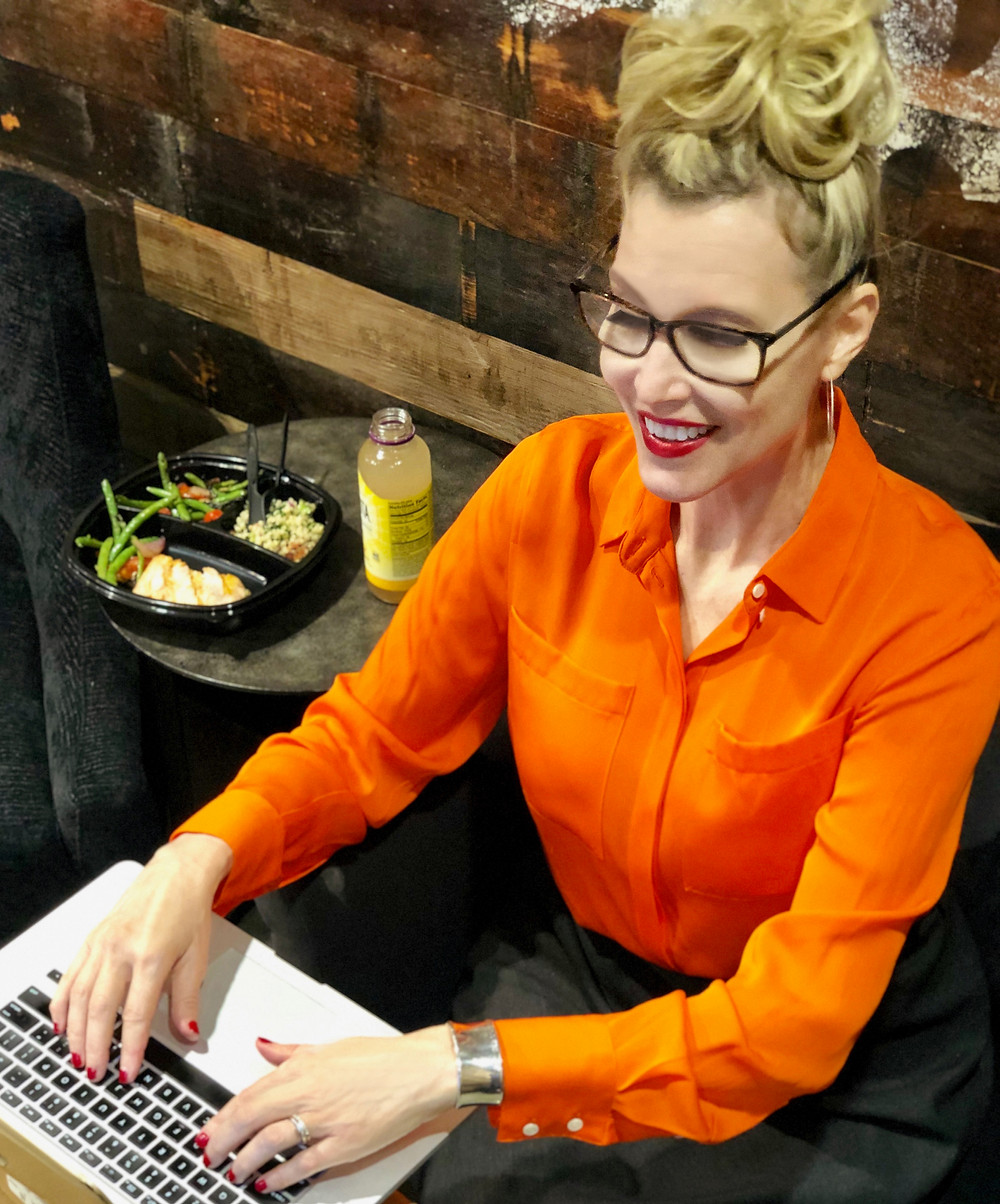 Woman on computer eating lunch