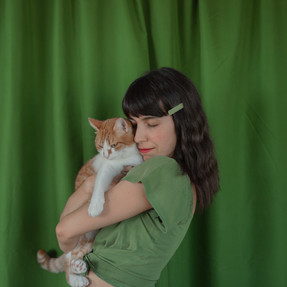 Woman wearing hair clips holding a cat.j