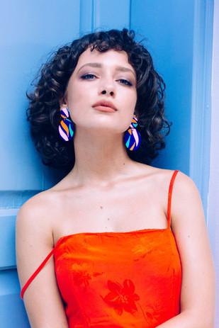 Model wearing blue wavy drop earrings.jp