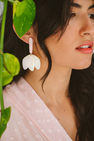 Model wearing floral drops behind a plan