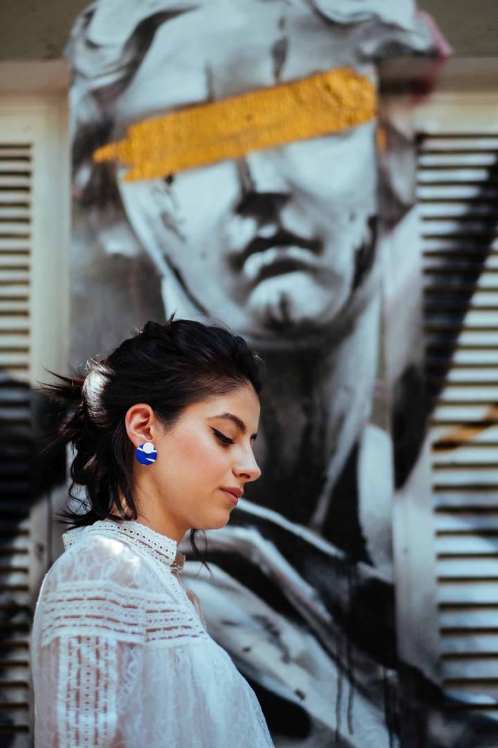 Model wearing blue stud earrings posing