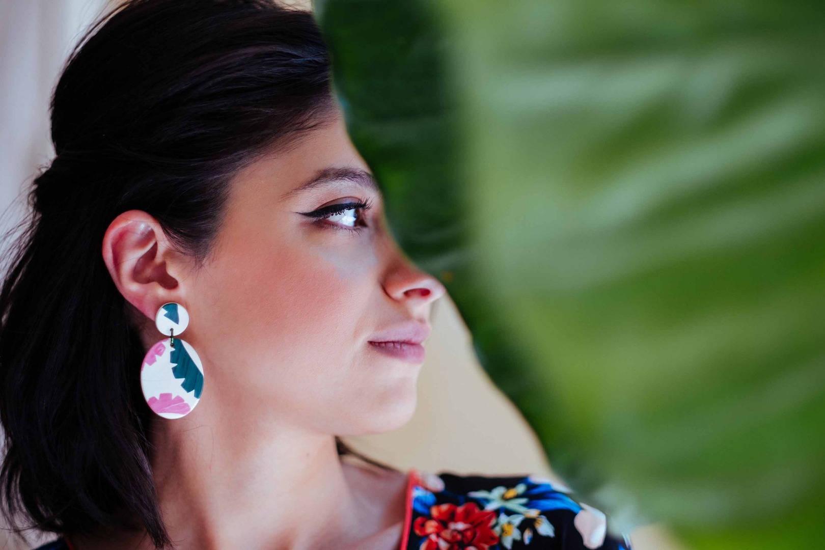 Model wearing colorful drop earrings pos