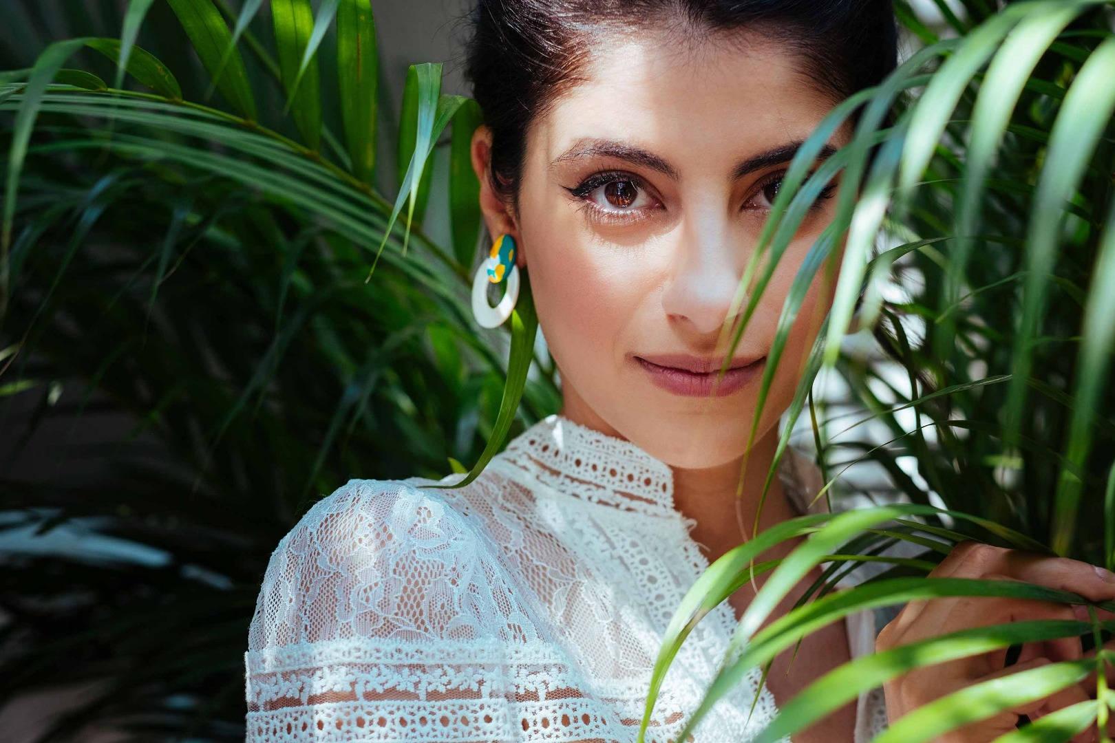 Model wearing stud earrings posing betwe