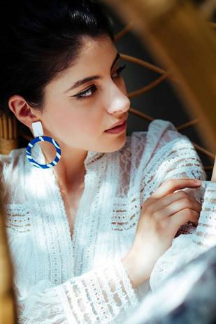 Model wearing blue hoop earrings posing