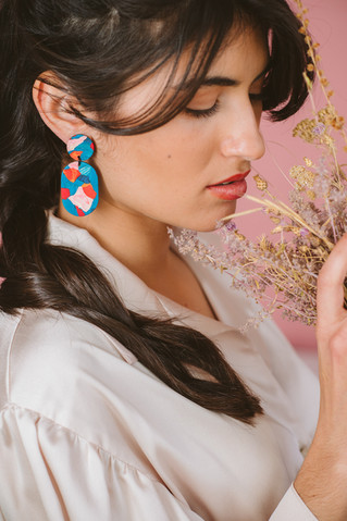 Model on colorful drop earrings holding