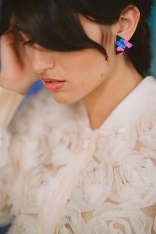 Model wearing triangle stud earrings.jpg