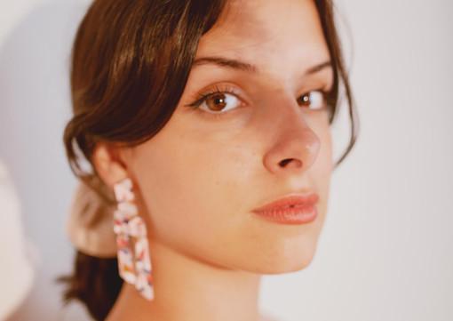 Side view of a model wearing drop earrin