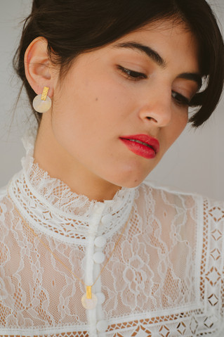 Model wearing gold-plated earrings and n