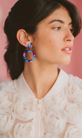 Model wearing colorful circle drop earri