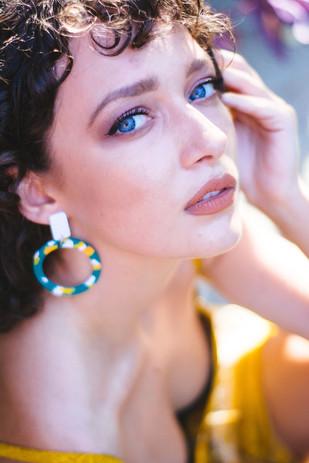 Model wearing green statement earrings c