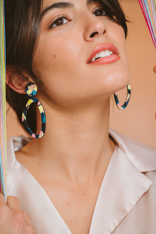 Model wearing asymmetrical hoop earrings