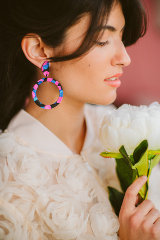 Model on large hoop earrings holding pla