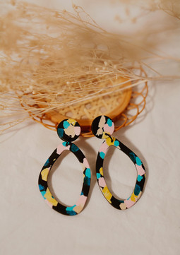 Asymmetric hoop earrings on a table.jpg