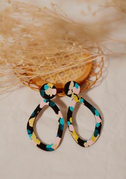 Asymmetric hoop earrings on a table.jpg