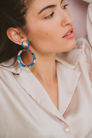 Model on colorful hoop earrings posing.j