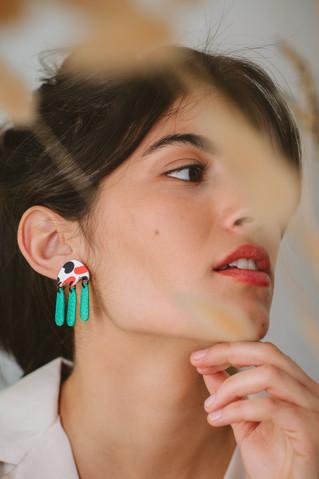 Model wearing delicate colorful earrings