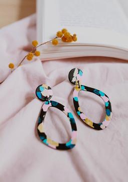 Colorful asymmetric earrings on a table