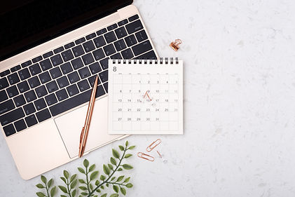 Calendar with rose gold pen on laptop on