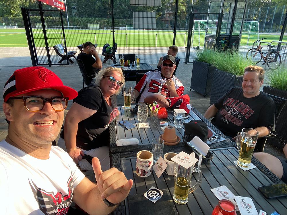 4 Personen am Tisch mit Bier und essen im Park