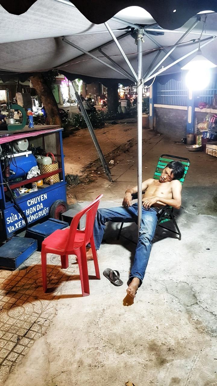 A mechanic sleeping on the side walk in Ho Chi Minh City, Vietnam