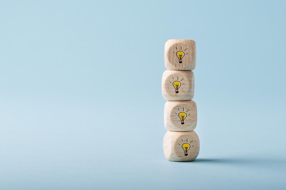 Petits dés de bois empilés pour former une tour, sur lesquels apparait l'image d'une ampoule illuminée