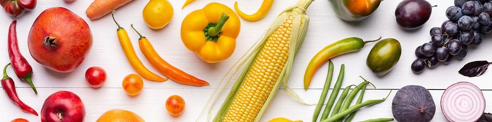 Fruits et légumes sur une surface plane, disposés de manière à créer un dégradé de couleurs.
