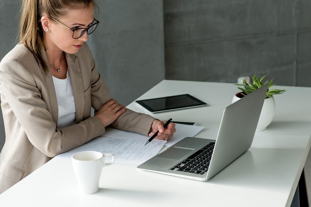 Femme assise à un bureau, devant un ordinateur, en tenant un crayon entre ses mains