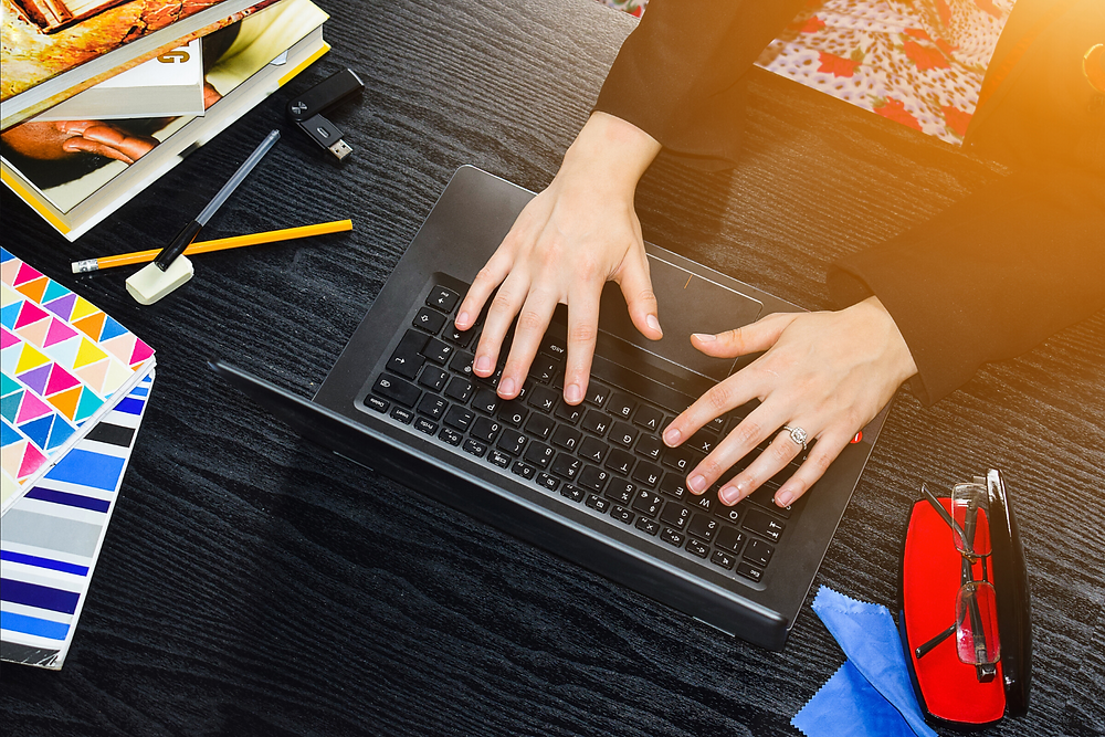 Mains tapant sur le clavier d'un ordinateur, entourées de cahier et crayons.