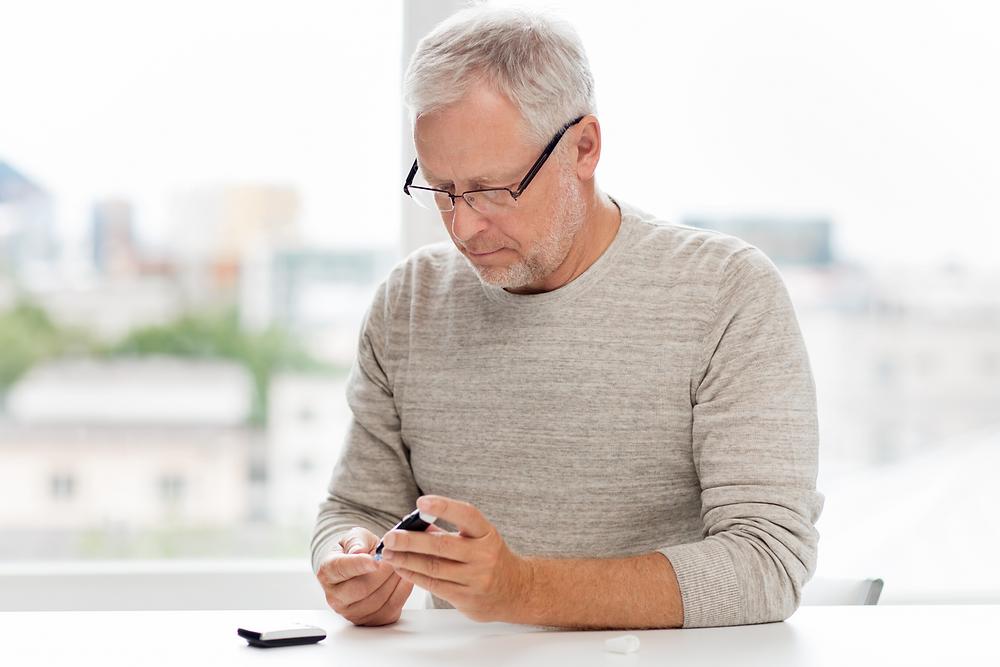Homme dans la soixantaine assis à une table et mesurant sa glycémie