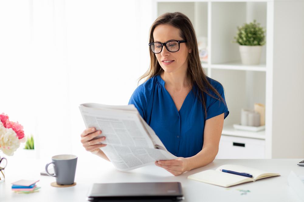Femme assise à une table lisant le journal